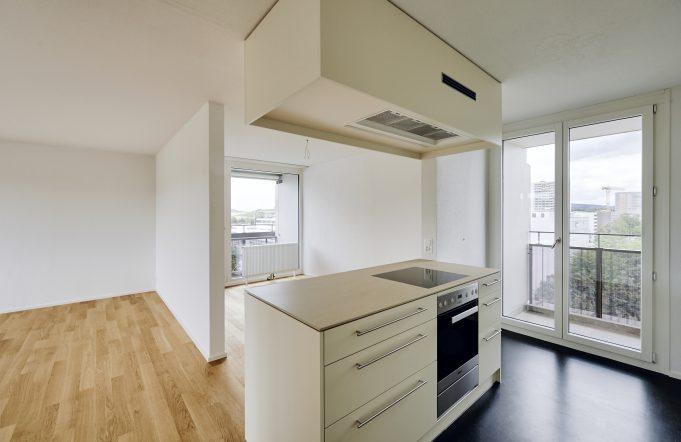Das Bild zeigt eine Wohnküche. In der Mitte des Bildes befindet sich eine helle Kochinsel, die in den Wohnbereich übergeht. Rechts neben der Wohnküche ist ein Balkon sichtbar.